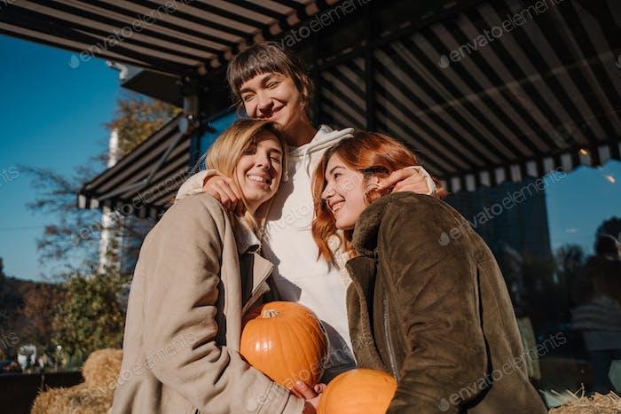 Girls holds pumpkins in hands. Outdoor photo