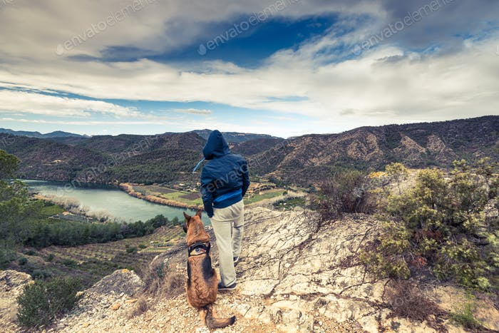 Traveller and dog looking over river
