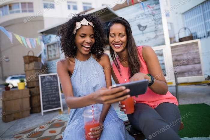 Happy friends using mobile phone near food truck