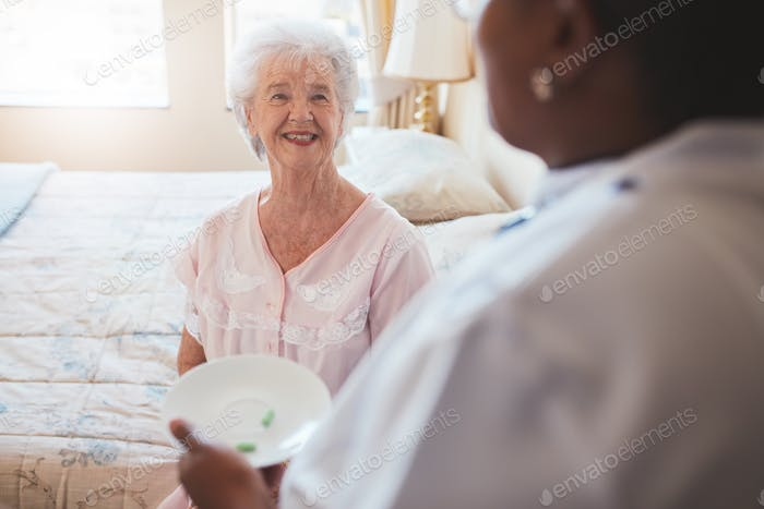 Senior woman on bed with nurse giving medication