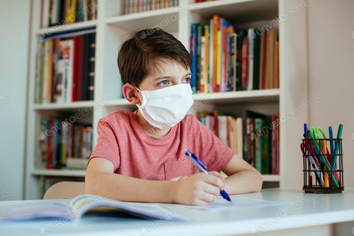 Young student wearing surgical mask working on school assignments on his own.