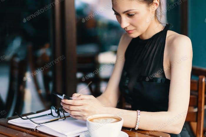 Schöne Business-Dame trinken Kaffee und nutzt Telefon