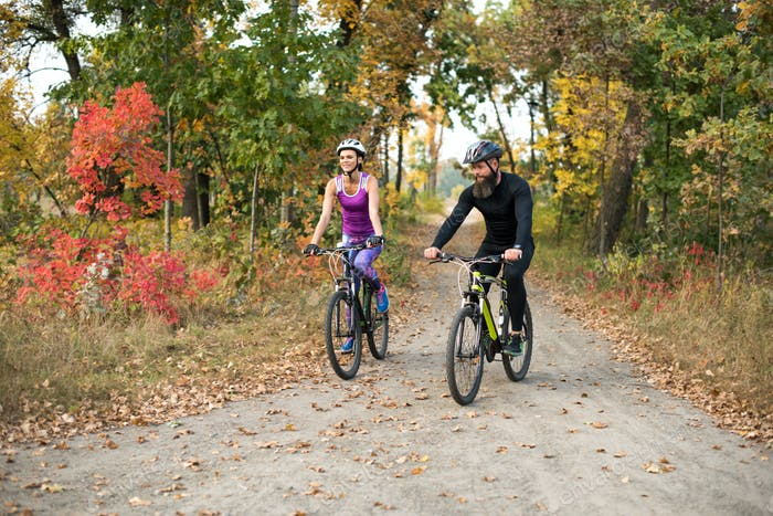 Couple of people cycling in autumn park