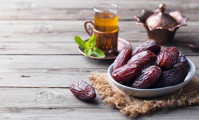 Medjool Dates in a Bowl with Tea. Ramadan Kareem. Grey Wooden Background. Copy Space.