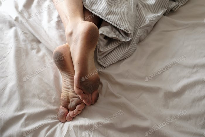 Dirty bare feet of a sleeping person showing out of the blanket