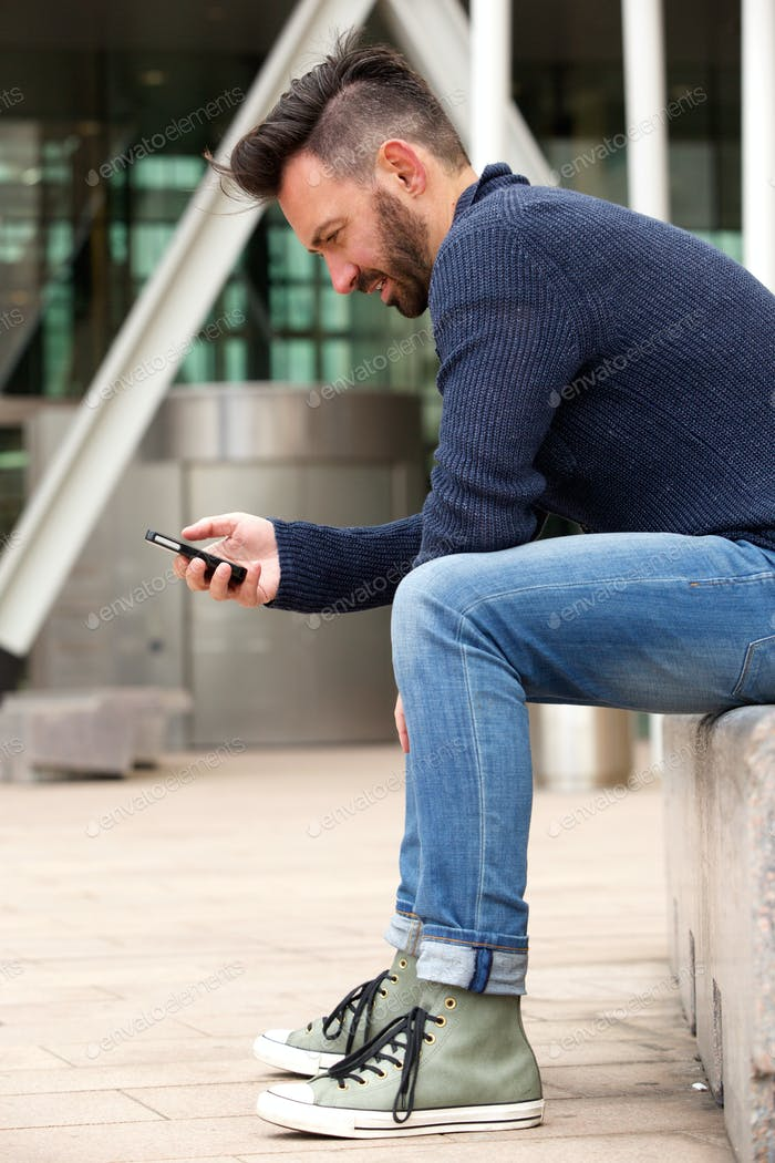 Handsome mature man sitting by the street using cellphone