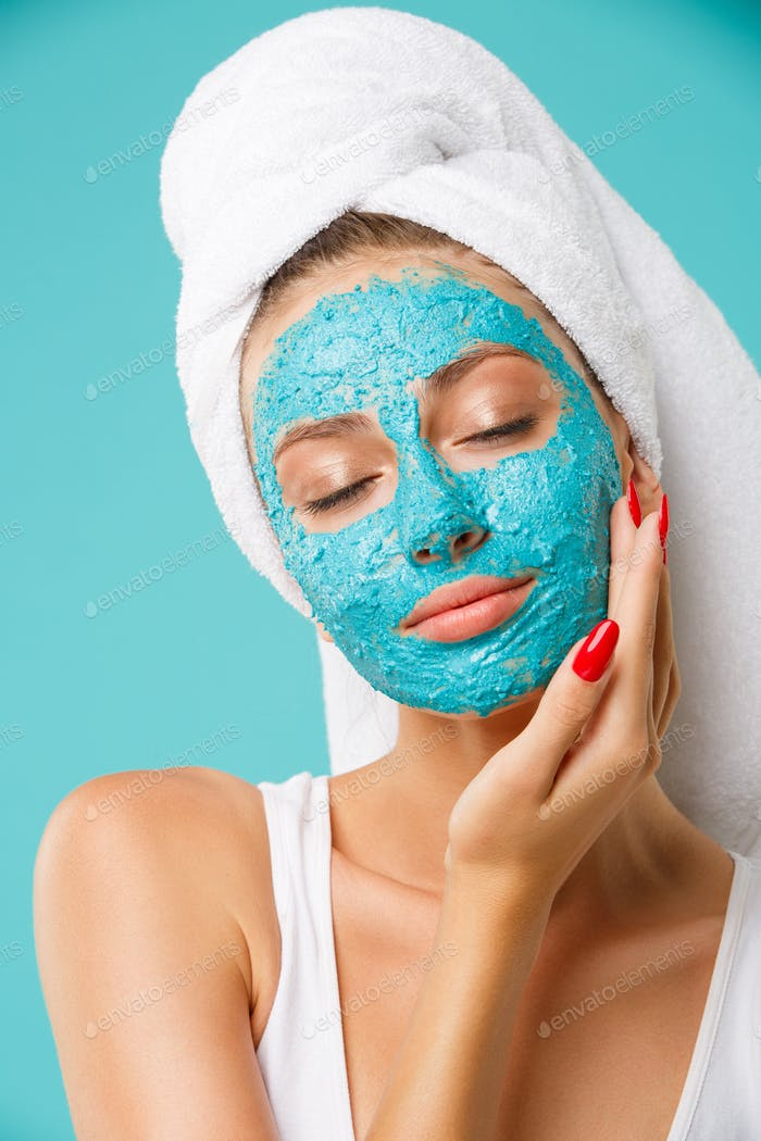 Beauty treatment - woman applying clay face scrub mask