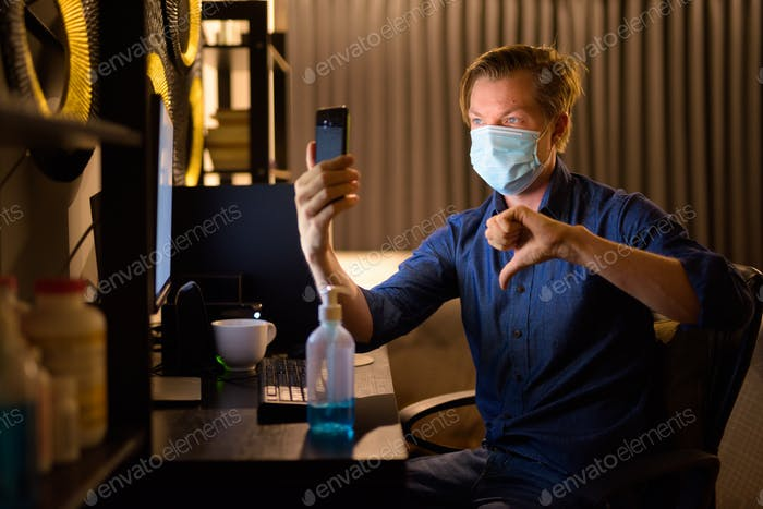 Young businessman with mask giving thumbs down and video calling while working from home late at