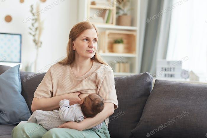Porträt von Nachdenklich Reife Mutter Stillen Kind