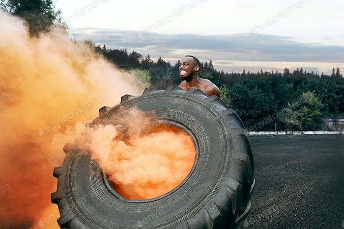 Schöner muskulöser Mann Flipping großen Reifen im Freien.