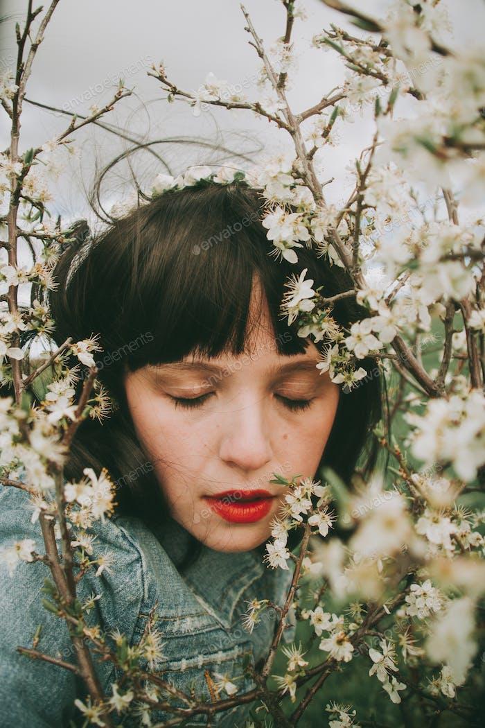 Schöne junge Frau posiert in der Nähe von Frühlingsblumen