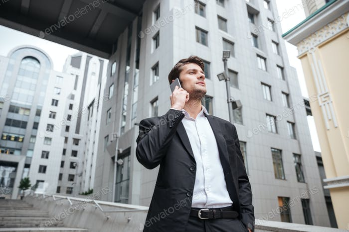 Serious young businessman talking on cell phone near business center