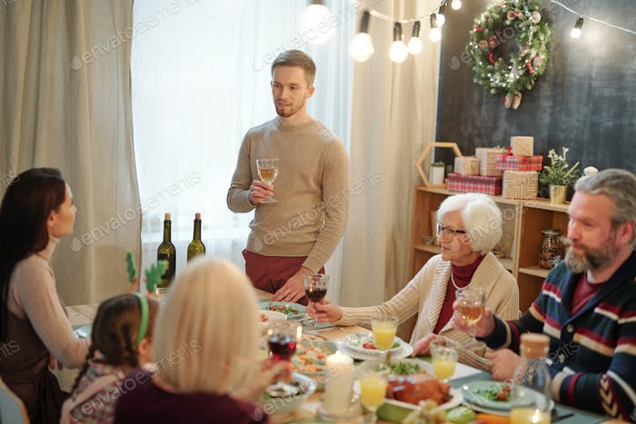 Young man with glass of wine making toast by served table in front of his family