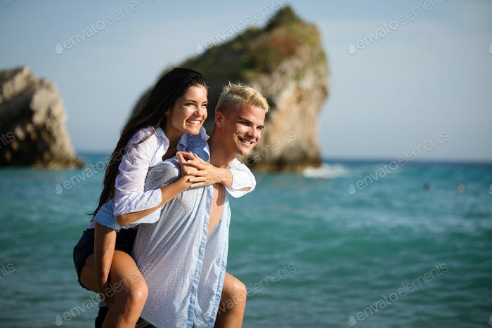 Happy cheerful couple having fun on a tropical beach at sunset