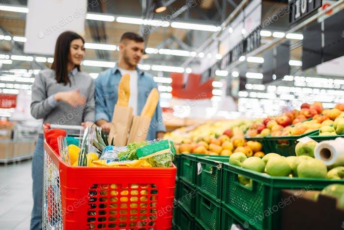Pareja con carro en supermercado, departamento de frutas