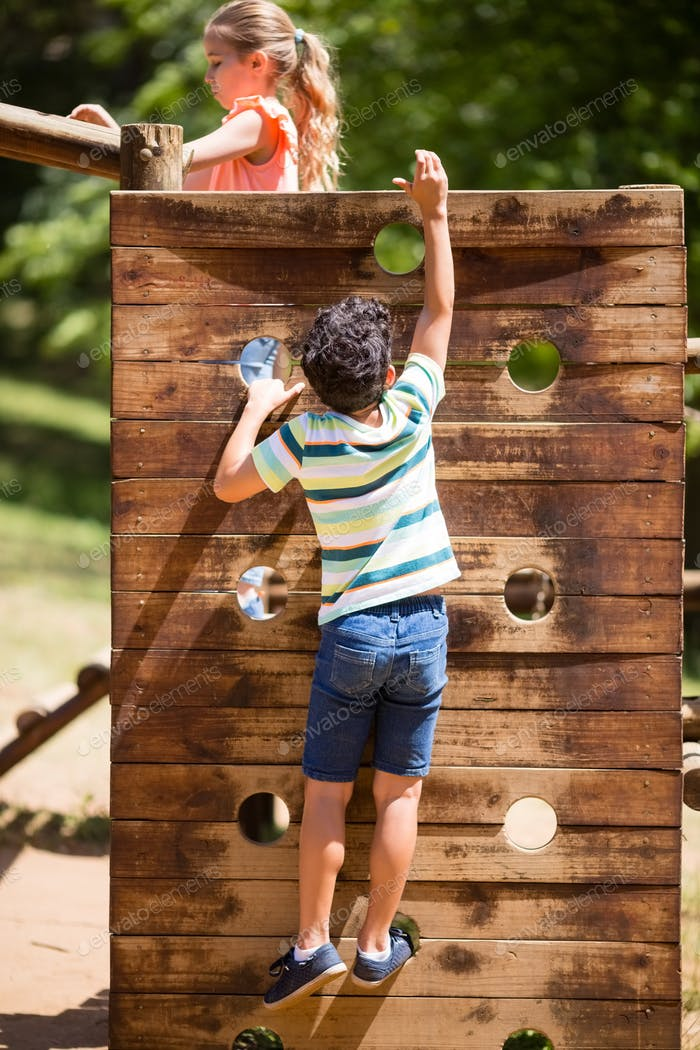 Boy climbing on a playground ride in park