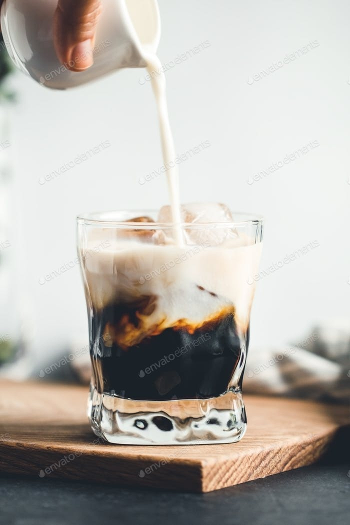 Pouring milk in a glass with espresso and iced cubes in a modern kitchen in the morning.