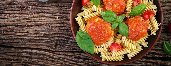 Fusilli  pasta with meatballs in tomato sauce and basil in bowl.