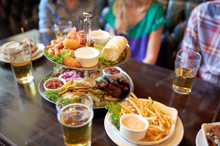 people sitting at table with food and beer at bar