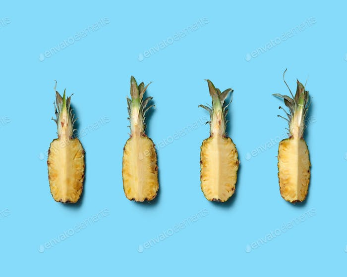 Pieces of a healthy pineapple on a blue background with space for text. Tropical fruit. Flat lay