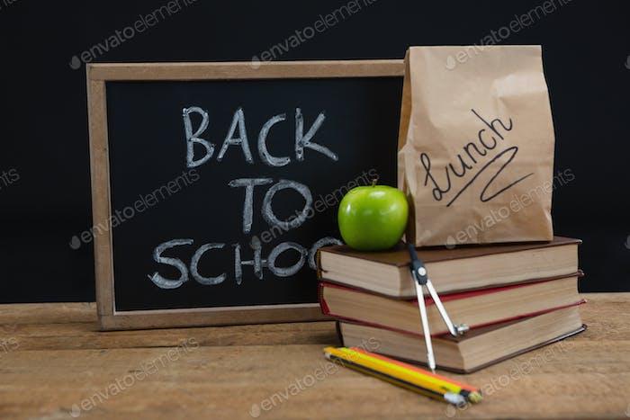 Lunch-Papiertasche, grüner Apfel und Schiefer mit Text zurück zur Schule auf Holztisch