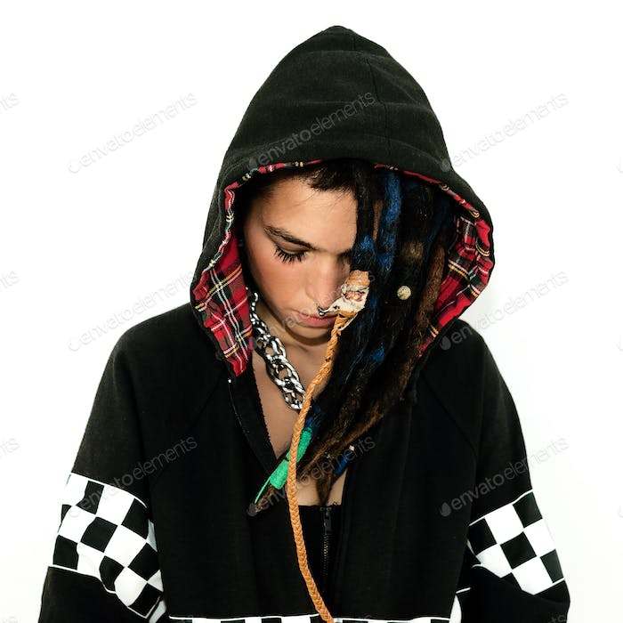 Girl in a sweatshirt with dreadlocks and piercings. Fashion acce