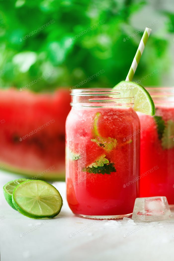 Fresh red watermelon smoothie in glass jar with straw, ice, mint and lime on light background, copy