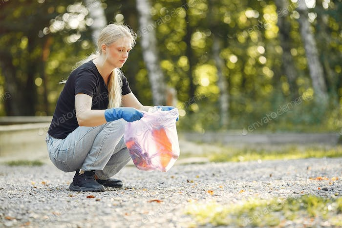 Woman collects garbage in garbage bags in park