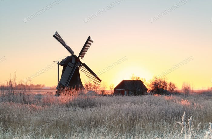 sunrise over frosted meadow and windmill