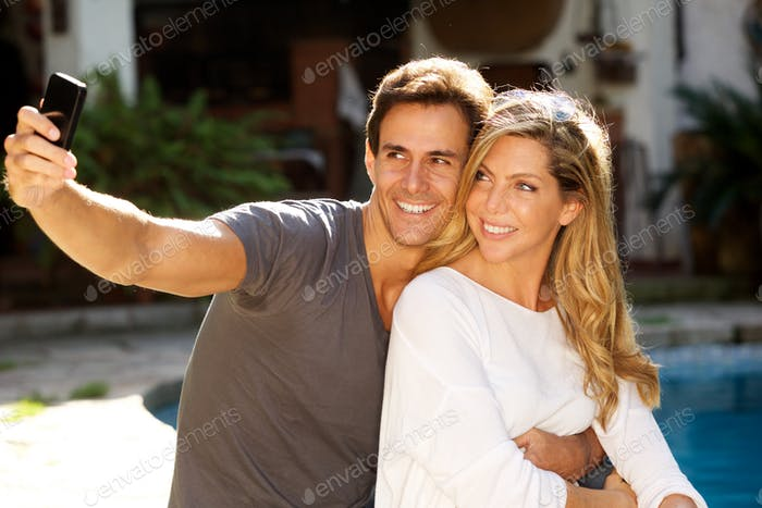happy couple sitting together by pool taking selfie