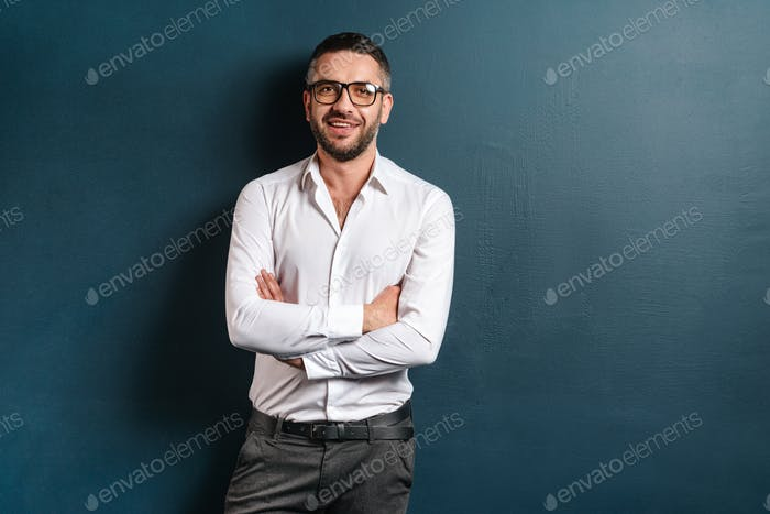 Handsome cheerful man standing over dark blue background