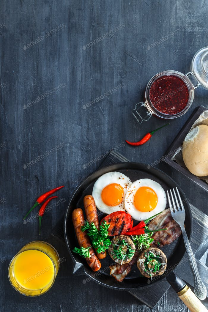 Englisches Frühstück mit Spiegeleier, Würstchen, Speck, Pilzen, Marmelade und Orangensaft, Copyspace