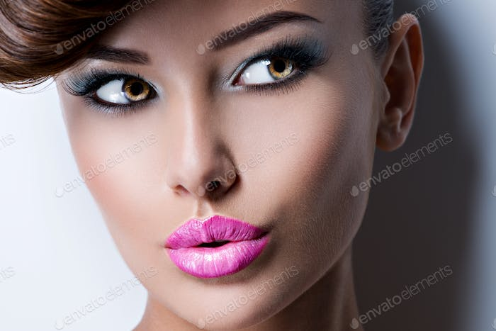 Portrait of a pretty girl model with pink lipstick looking away