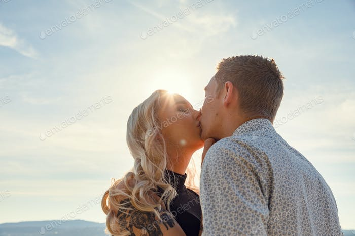 Romantic couple kissing on beach against the sun