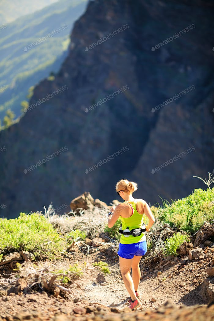 Woman walking running in rocky mountains on summer day