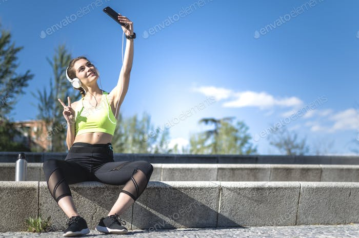 happy woman taking selfie in a park with sportswear after running and headphones