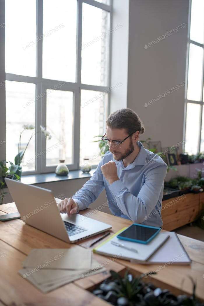 Attentive man with glasses looking at laptop.