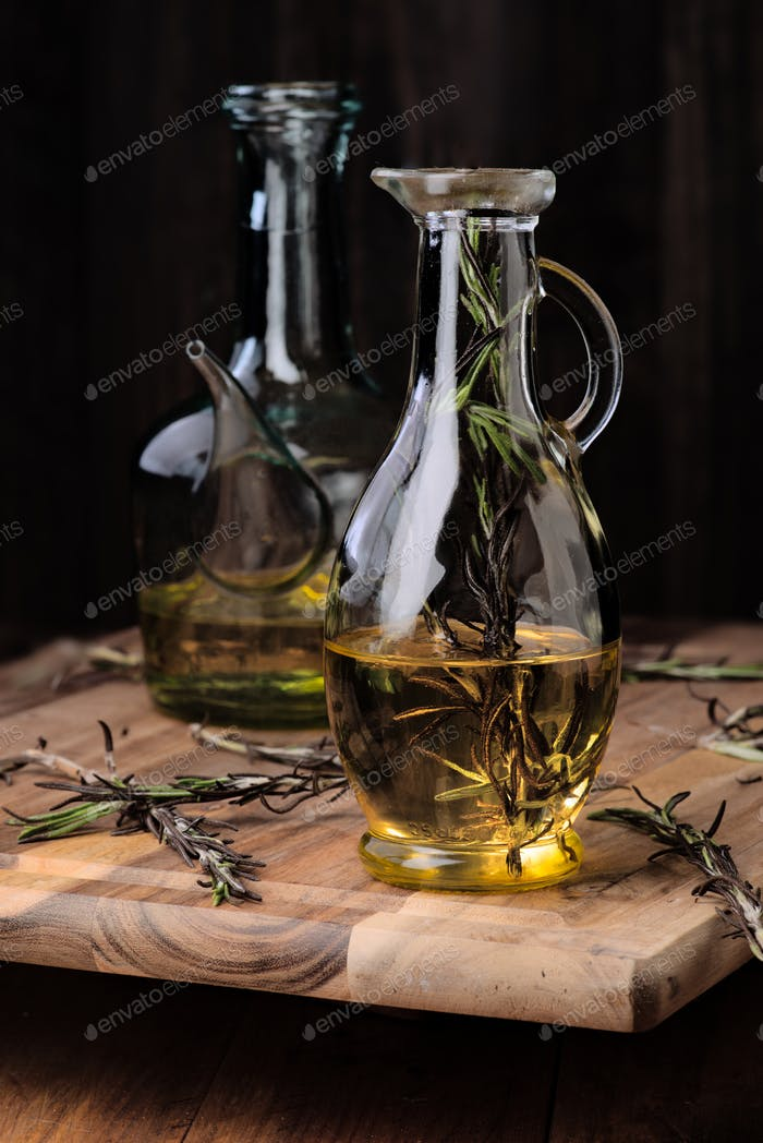 Spanish olive oil of intense color and branches of rosemary on rustic wood