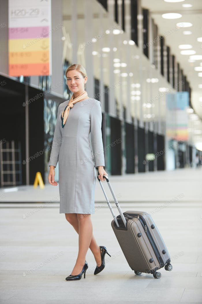 Elegant Stewardess with Suitcase in Airport