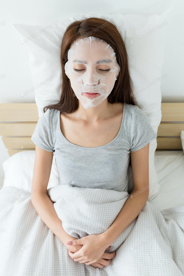 Woman do facial masking on bed