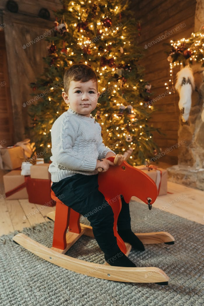 Shot of a cheerful kid riding on rocking horse