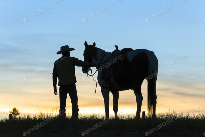 Cowboy standing next to his horse in a Prairie landscape at sunset.