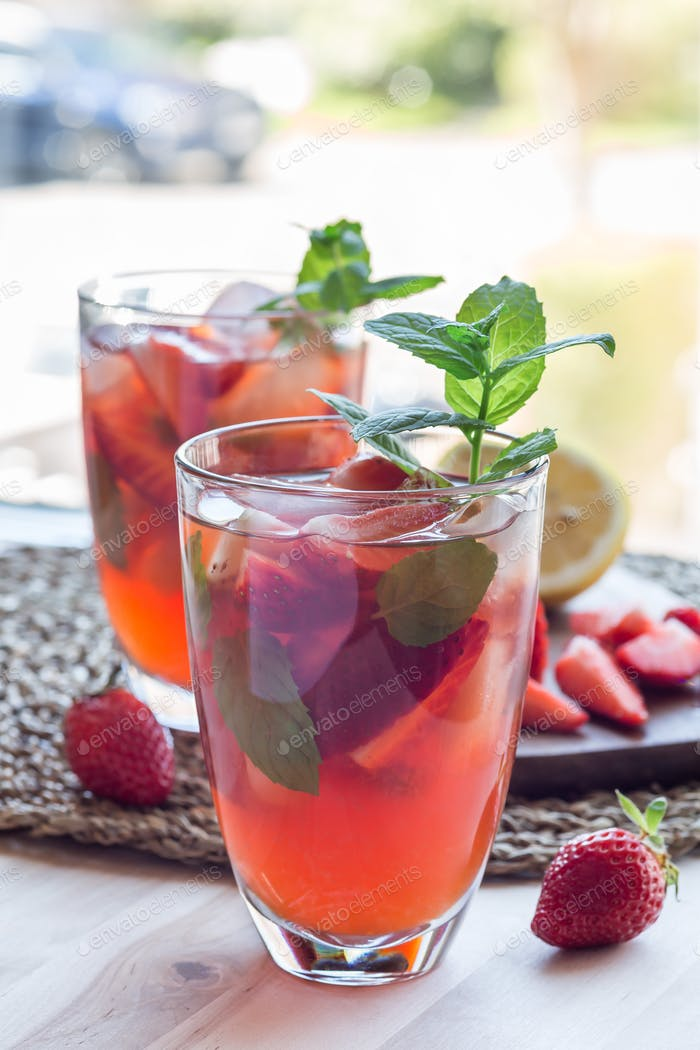 Homemade iced tea with strawberries and mint, vertical