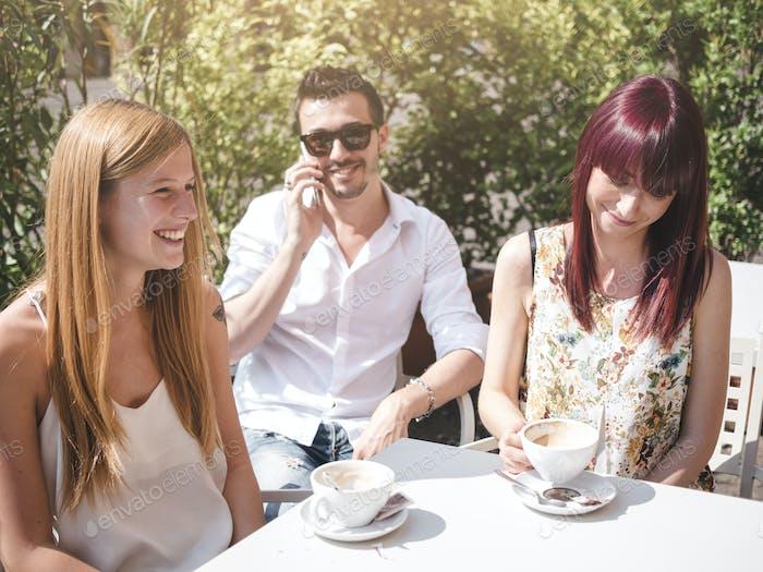 Freunde zusammen reden und einen Kaffee in einer Bar im freien in italien