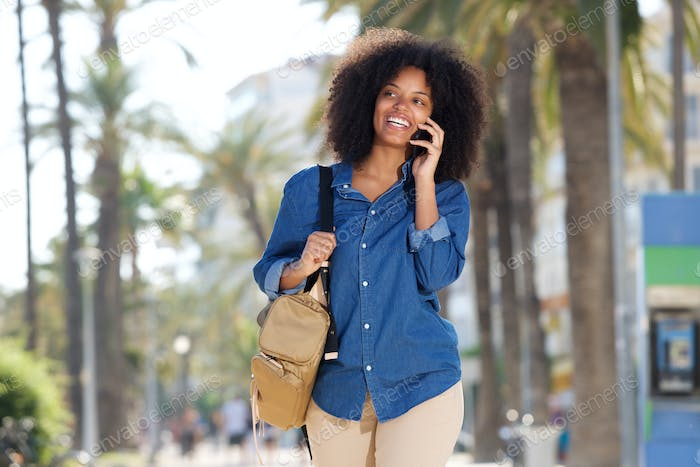 Happy woman walking by palm trees on mobile phone