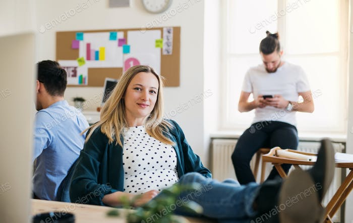 Portrait of young relaxed businesswoman with colleagues in a office, feet on desk.