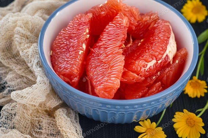 Scheiben frische Bio-Grapefruit in einer Schüssel mit Ringelblumenblüten in der Nähe