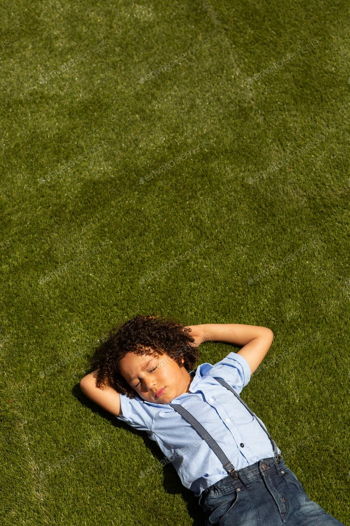 High angle view of a mixed-race schoolgirl relaxing in the school playground on a sunny day