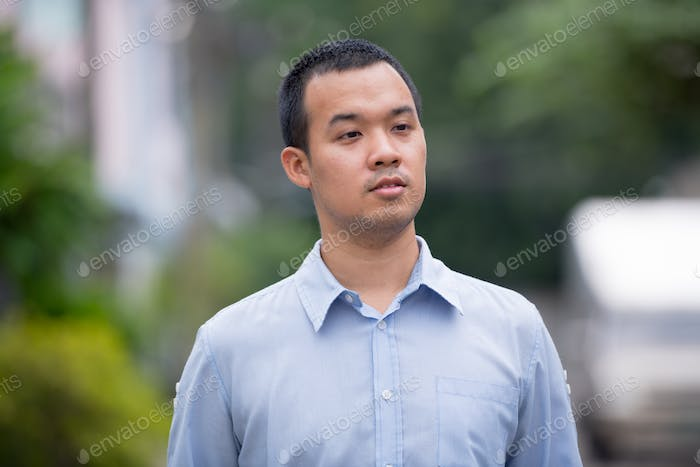 Portrait of Asian businessman thinking and looking away outdoors