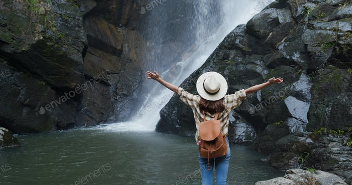 Woman look at the waterfall in forest